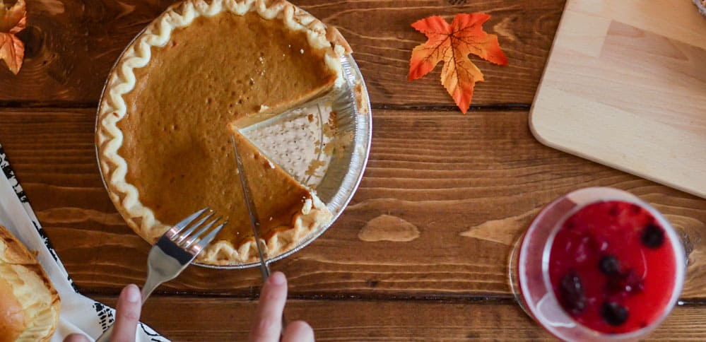 Pumpkin pie being cut and served on a table